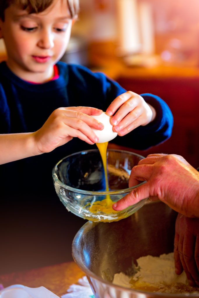 Boy cracking egg into bowl