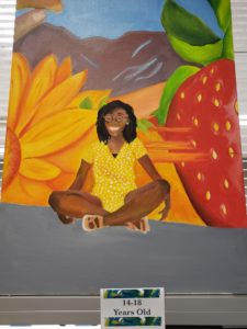 original painting of a girl sitting with sunflower and strawberry in background