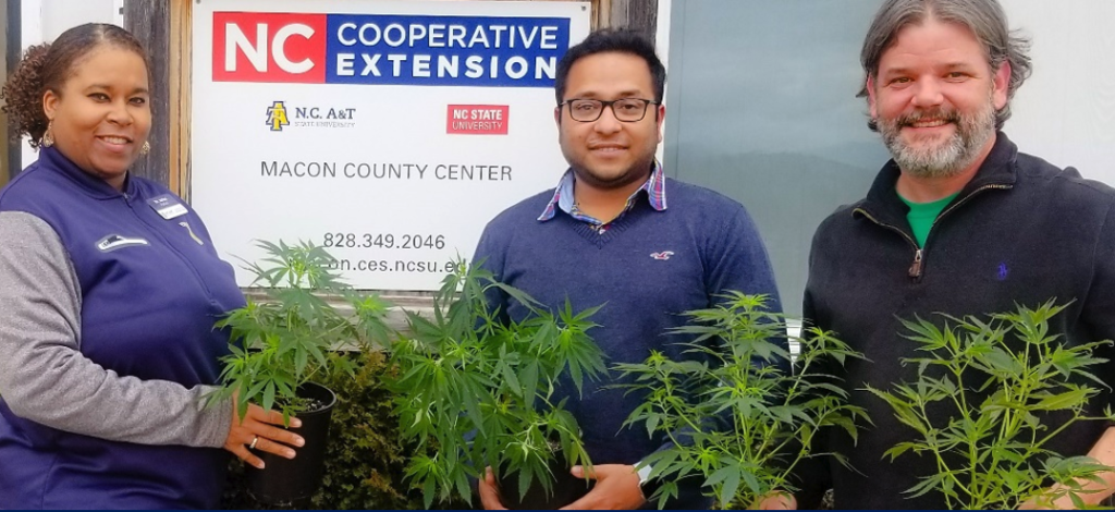 Three individuals holding plants in front of an N.C. Cooperative Extension logo banner