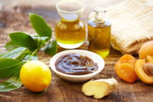 table with fresh lemon, oils and sugar scrub in bowl