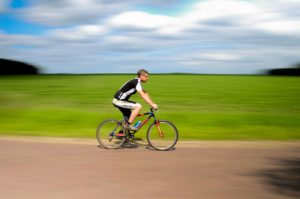 Man riding a bike down a rode on a sunny day