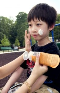 young-boy-was-receiving-a-reapplication-of-a-coating-of-protective-sunscreen-by-his-mother