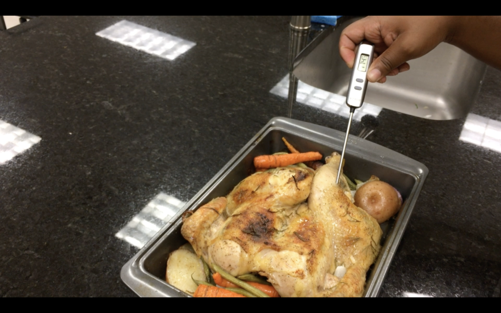 Checking the temperature of a roasted chicken