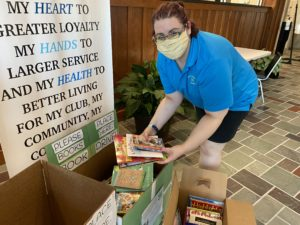 4H Program Assistant looking at book drive donations