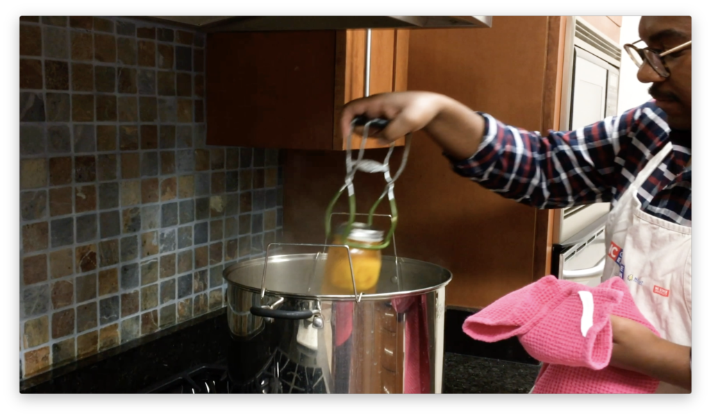 Person performing Water Bath Canning of Peaches