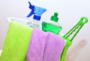 Cleaning supplies and washcloths in a bucket
