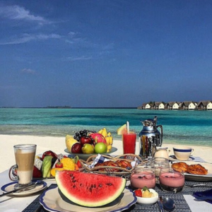fresh fruit meal laid out on blanket beach scene