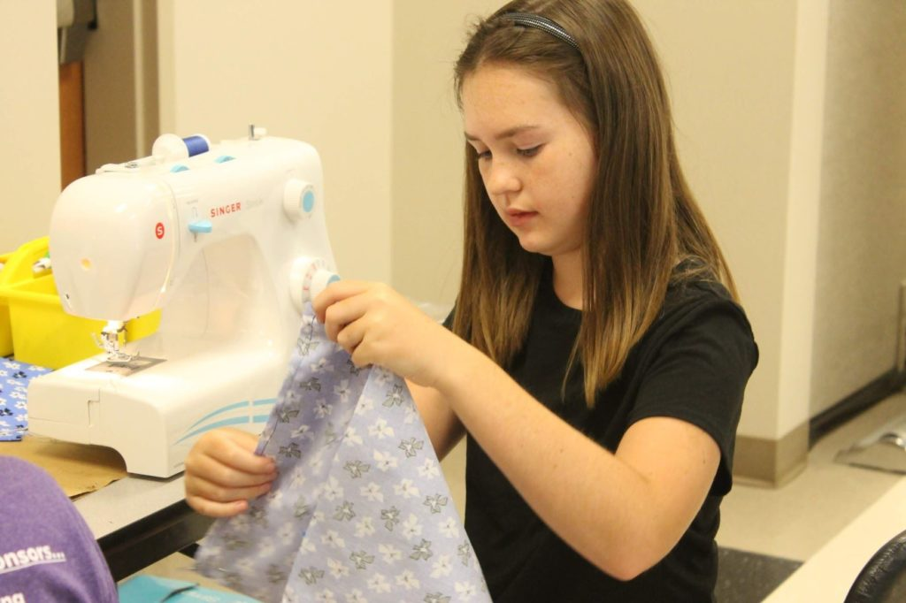 4-H youth participating in sewing camp and looking at project