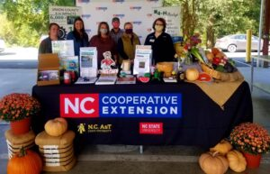 6 people standing behind a table that says NC Cooperative Extension