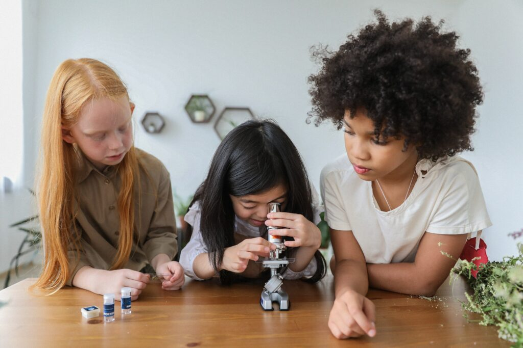 Three girls hovered over a microscope
