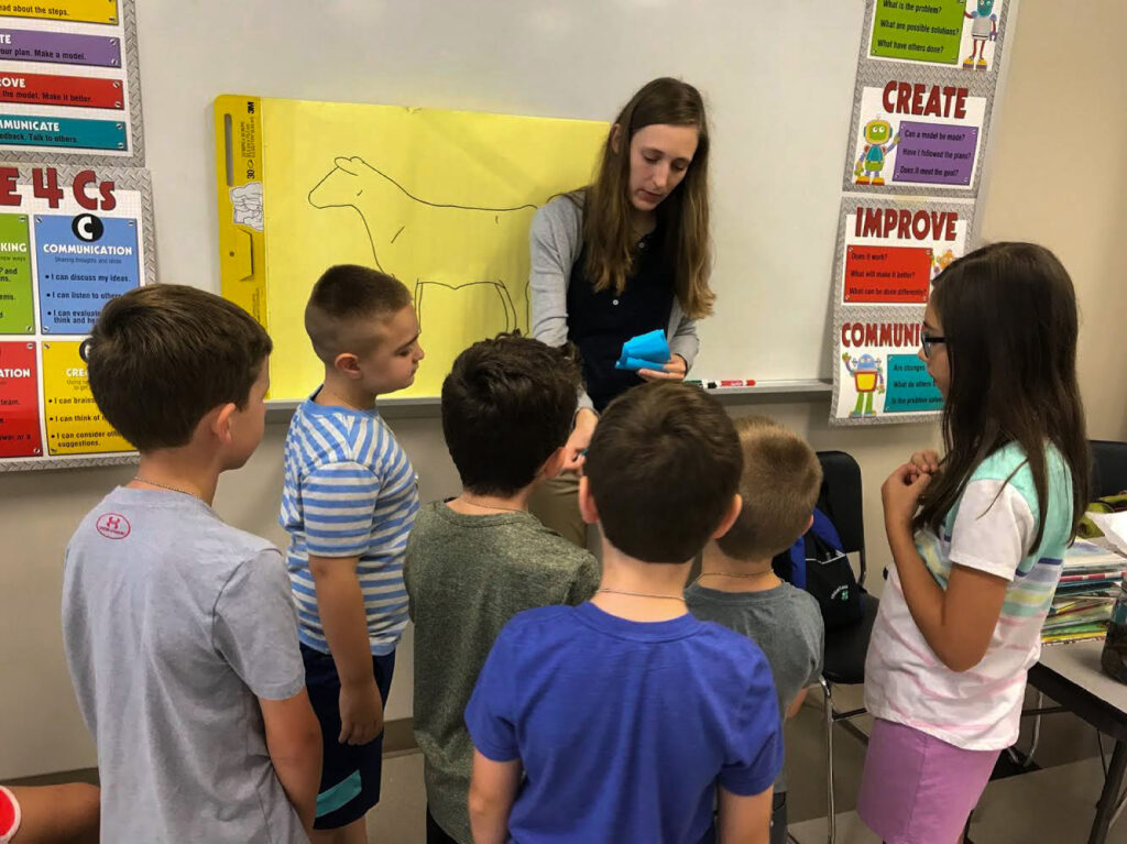 Children standing around teacher as she gives instructions for activity