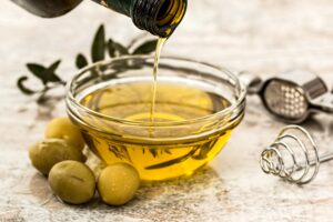 Yellow Olive Oil Being Poured into a Small Glass Bowl