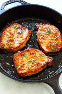 3 pork chops in a black skillet pan