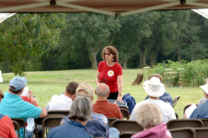 Woman in Red Shirt Teaching People about Agriculture