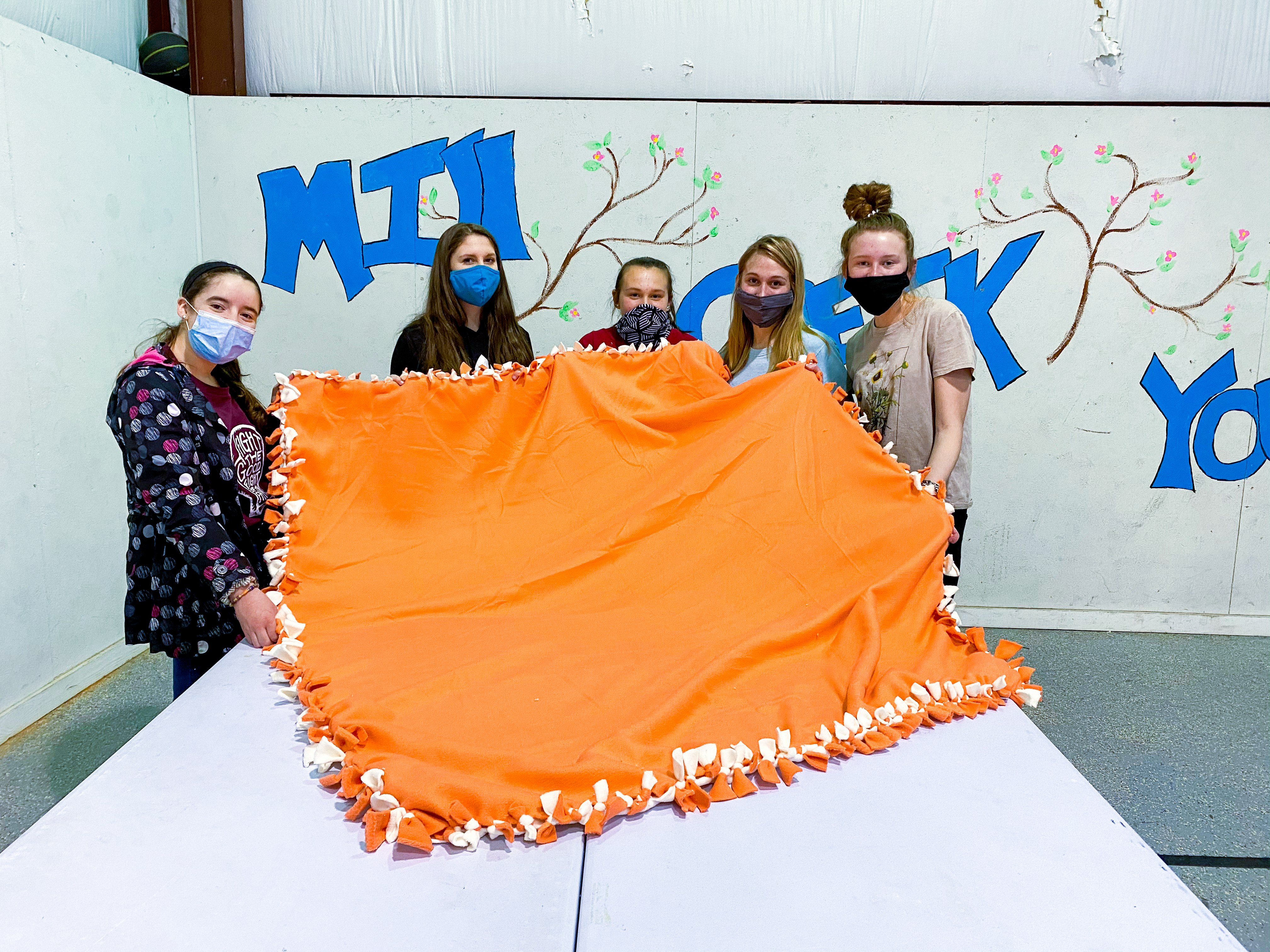 5 children standing with a large orange blanket in front of them.