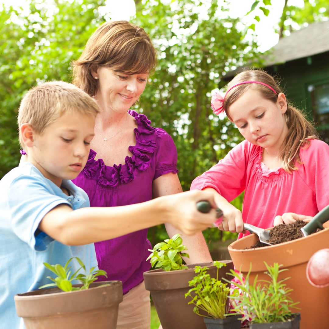 Mother helping her children plant container gardens