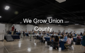 We Grow Union County in front of picture of people at a dinner
