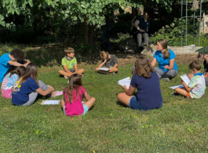 Children sitting in circle learning about animals